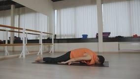 Een mensenyoga maakt zich het gezonde uitrekken Jonge mens het praktizeren yoga binnen Kerel die een asana op zwarte mat binnen d stock video