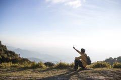 Een mensenzitting bovenop berg Stock Afbeelding