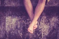 Een mensenzitting en ontspant op cementmuur met benen die neer hangen Stock Fotografie
