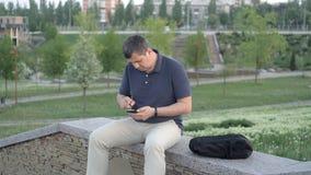 Een mensenzitting in het Park op een groene achtergrond, onbekend steelt zijn zak en loopt weg stock videobeelden