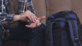 Een mensenzitting op een bank plaatst - omhoog en drukt een hand mechanisch horloge en zet het op zijn hand Dichtbij is een blauw stock video