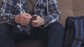 Een mensenzitting op een bank plaatst - omhoog en drukt een hand mechanisch horloge en zet het op zijn hand Dichtbij is een blauw stock footage