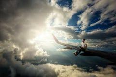 Een mensenzitting op de vleugel van vliegtuig Royalty-vrije Stock Fotografie