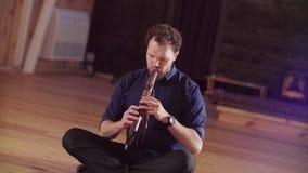 Een mensenzitting op de de vloer en het spelen fluit stock footage