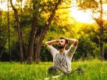 Een mensenzitting op gras in zich het park en het uitrekken Stock Afbeeldingen