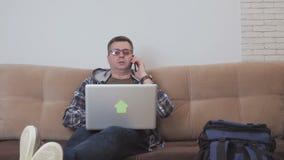 Een mensenzitting op middelbare leeftijd op een bank gebruikt laptop en het spreken op de telefoon, naast hem is een grote toeris stock video