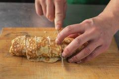 Een mes in zijn hand snijdt een broodje van rijst close-up op een houten raad royalty-vrije stock fotografie