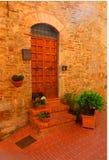 Een met panelen beklede houten deur in een steenhuis met ingemaakte installaties en bloemen in een Toscaanse heuvelstad stock foto