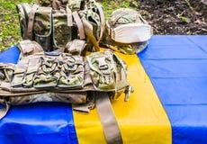 Een een metaalhelm en kogelvrij vest leggen op een blauwe gele vlag stock foto