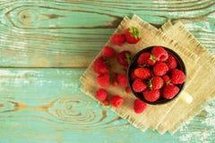 Een metaalkop met aardbeien en frambozen op de servetten op de blauw-witte houten achtergrond Royalty-vrije Stock Afbeelding