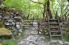 Een metaalpoort door een muur en een stijl over het, lood in een rotsachtige weg door bos stock foto's