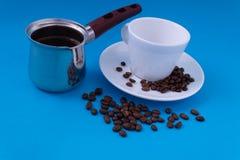 Een metaalpot van vers gebrouwen koffie bevindt zich naast witte schotels en opgestapelde koffiebonen stock fotografie