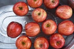 Een metaalton met water en appelen voor Halloween-custo wordt gevuld die royalty-vrije stock afbeelding