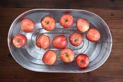 Een metaalton met water en appelen voor Halloween-custo wordt gevuld die stock afbeeldingen