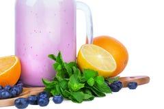 Een metselaarkruik met een purpere milkshake en heel wat citrusvruchten met groene munt, die op een witte achtergrond wordt geïso Royalty-vrije Stock Foto