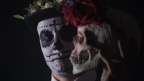 Een Mexicaanse mens met gezichtsverf en een hoed likt de schedel, 4k stock video