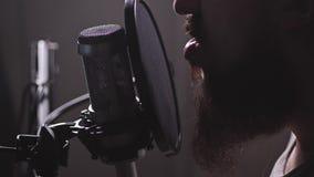 Een microfoon in de studio, een mens verschijnt, begint reciterend of te zoemen 4K langzame mo stock footage