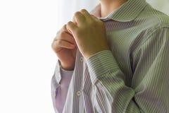 Een middelbare schoolstudent of de student snellen zijn overhemd, die naar school voor lessen gaan gaan stock fotografie