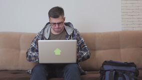 Een midden oude mensenzitting op een bank gebruikt een laptop computer, naast hem is een grote toeristenrugzak stock videobeelden