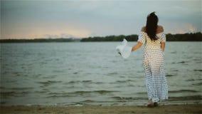 Een midden oude vrouw die zich bij waterrand bevinden en haar grote witte hoed uitstellen stock videobeelden