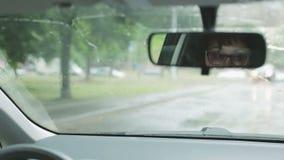 Een midden oude vrouw in glazen zit bij het stuurwiel van een auto stock footage