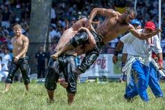 Een middengewichtsworstelaar is opgeheven skywards door zijn tegenstander bij het de Olie van Kirkpinar Turkse het Worstelen Fest stock afbeelding