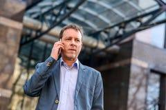 Een middenleeftijdszakenman met een telefoon Stock Afbeeldingen
