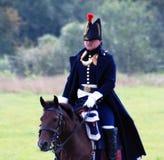 Een militair berijdt een bruin paard. Stock Foto's