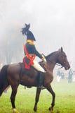 Een militair berijdt een bruin paard. Stock Fotografie