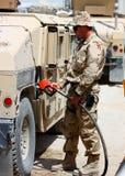 Een militair die een voertuig bijtankt stock foto's