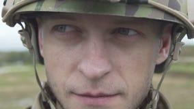 Een militair in een legerhelm en hoofdtelefoon van de radio stock footage
