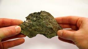 Een mineraal van vuile groene kleur met een prominente granaatsteen stock video