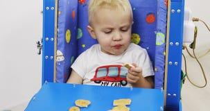 Een miniatuurauto met een lijst Het kind eet koekjes en zit in het stuk speelgoed stock video