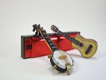 Een miniatuurbanjo en een miniatuur akoestische gitaar propped omhoog op een rode harmonika stock foto