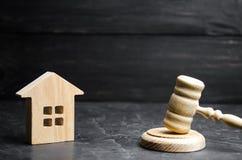Een miniatuurblokhuis en een hamer van de rechter De veiling om te kopen/verkoopt een huis Gedwongen uitzetting en inbeslagneming stock afbeeldingen