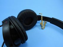 Een miniatuursaxofoon propped omhoog in een zwarte hoofdtelefoon royalty-vrije stock foto's