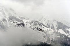 Een mistig misteric die panorama van de bergen van Alpen gedeeltelijk met de sneeuw op bewolkt Oktober worden behandeld royalty-vrije stock afbeeldingen