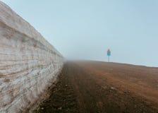 Een mistige modderige weg naast een muur en verkeersteken royalty-vrije stock afbeeldingen