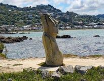 Een Moai-standbeeld op de bank van Lyall-Baai, Wellinton, Nieuw Zeeland Dit standbeeld is onlangs gebroken door vandalen stock fotografie