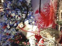 Een model van het rendier van de Kerstman bevindt zich voor een verfraaide Kerstmisboom stock afbeelding
