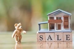 Een modelhuismodel en Teddy Bear worden geplaatst op houten woordverkoop als achtergrond bedrijfsconcept en onroerende goederenco Stock Foto