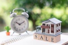 Een modelhuismodel wordt geplaatst op houten woordverkoop Als achtergrond royalty-vrije stock afbeelding