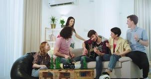 In een modern huis in een groot bedrijf hebben de vrienden prettijd die samen op een gitaar spelen drinkt bier en het genieten va stock videobeelden