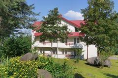 Een modern huis met witte muren en een betegeld dak die zich in het midden van de schilderachtige aard met een groen gazon en een Royalty-vrije Stock Foto's