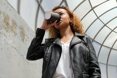 Een modern jong Afrikaans-Amerikaans meisje in een leerjasje drinkt koffie of een andere drank van een zwart glas op royalty-vrije stock foto