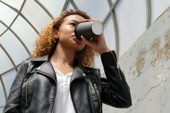 Een modern jong Afrikaans-Amerikaans meisje in een leerjasje drinkt koffie of een andere drank van een zwart glas op de straat Li stock foto