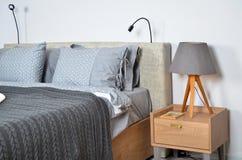 In een modern slaapkamerbed, hoofdkussens en bedlampen royalty-vrije stock foto