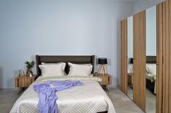 In een modern slaapkamerbed, hoofdkussens en bedlampen royalty-vrije stock afbeeldingen