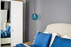 In een modern slaapkamerbed, hoofdkussens en bedlampen stock afbeeldingen
