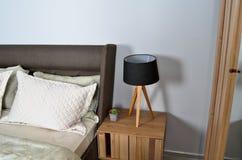 In een modern slaapkamerbed, hoofdkussens en bedlampen stock foto's